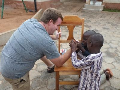 A volunteer arm wrestling children in Ghana