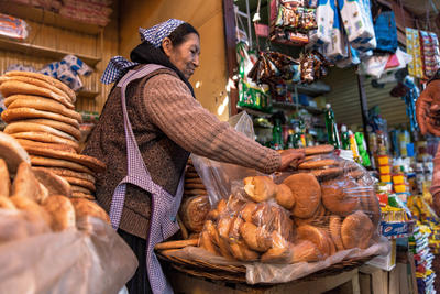 A bread-maker sells bread at her stand in the La Cancha, the central market of Cochabamba, Bolivia