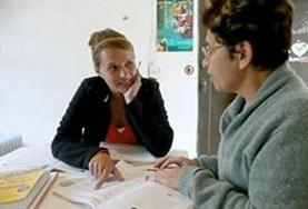 A Spanish language course volunteer discusses the work with her teacher