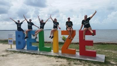 Projects Abroad volunteers in Belize sit on top of a sign during free time at their Projects Abroad placement