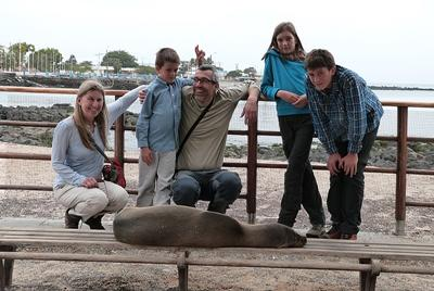 Volunteers in the Galapagos smile behind a sea lion in San Cristobal