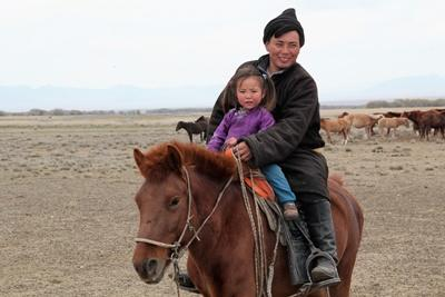 Nomad man and child ride a horse in Mongolia