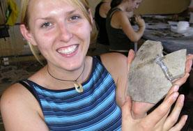 A volunteer holds up a fragment dug up during an Archaeology placement
