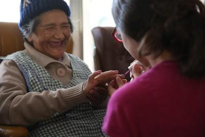 A resident of a retirement home in Cochabamba receives a manicure from a Projects Abroad Care volunteer during a community day