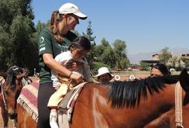 Equine therapy volunteer and child riding a horse in Bolivia