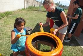 Care volunteer and child painting a tyre in Argentina