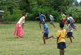A childcare volunteer plays a game with local children in Fiji to help with improving their motor skills.