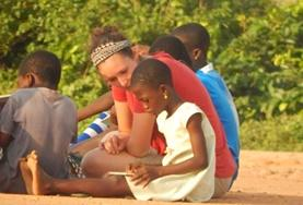 A Care volunteer reads a book with a young student in Ghana.