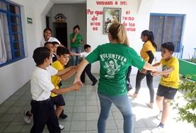 A childcare volunteer in Mexico leads children through an activity to help stimulate their physical development and promote teamwork.