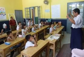 A childcare volunteer teaches students at a school for the deaf in Myanmar.