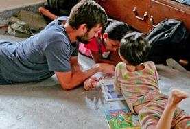 A Care volunteer reads to children at a placement in Nepal