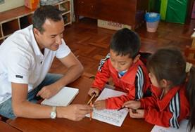 A Care volunteer assists children with their school work at a placement in Peru