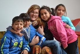 A Care volunteer poses with children at a placement in Romania