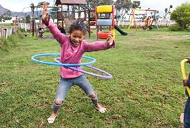 A young child plays with hula hoops on a playground at our volunteer childcare placement in Cape Town, South Africa.