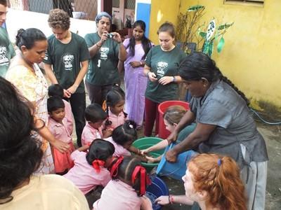 Projects Abroad volunteers clean the local children's hands