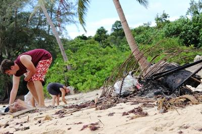 Projects Abroad conservation volunteers work together to clean a beach in Cambodia