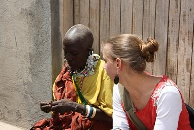 A volunteer sits with a Maasai woman in Tanzania
