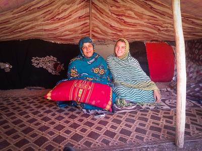 A local woman and a volunteer sitting in a Moroccan tent