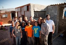 Volunteers and local people from a South African township work on building houses to benefit the community.