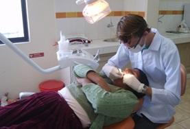 A dentist examines the teeth and gums of a patient