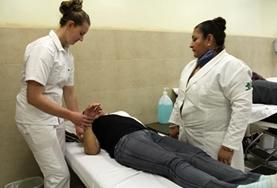 A local staff member supervises as a Nursing Elective intern works with a patient at a hospital in Mexico.