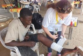 An intern completing her Nursing Elective in Togo assists with bandaging a child's wound during a medical outreach.