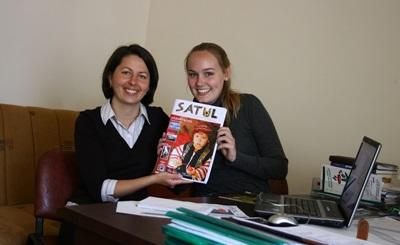 Volunteers hold up a newly printed copy of Satul magazine