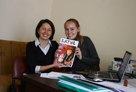 Journalism volunteers pose with a magazine at their placement in Romania