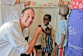 A Dentistry intern gives a child a high-five after a successful dentisty check-up at a hospital in Tanzania.