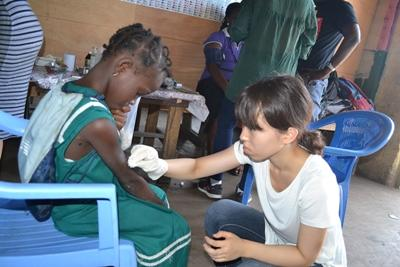Projects Abroad Medical volunteer from Japan treating a wound of a child during a medical outreach in James Town, Accra