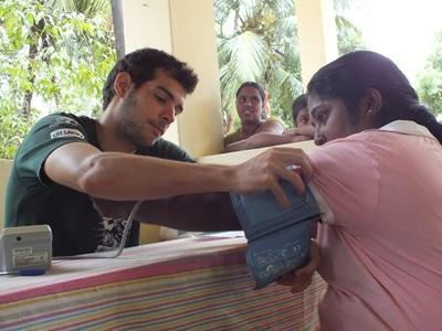 A local Sri Lankan woman gets her blood pressure checked by a volunteer