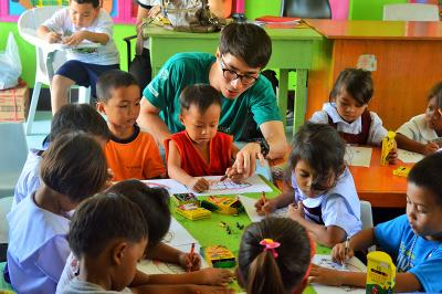 A male volunteer working with children on a placement in the Philippines