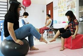 A Medical volunteer works on strengthening a young girl's foot muscles at our Physiotherapy internship in Vietnam