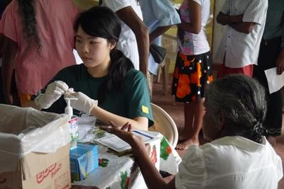 A Projects Abroad volunteer checks a Sri Lankan woman's blood sugar levels in Colombo.