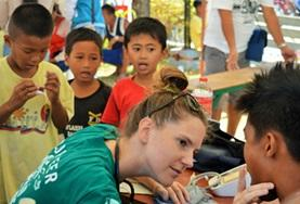 A Public Health intern assesses a child's health during a volunteer medical outreach in the Philippines.