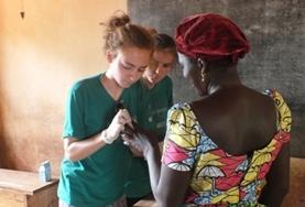 A Public Health intern assesses a local woman's wound during a medical volunteer outreach in Togo.