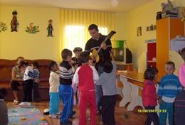 A professional Art Therapist volunteering in Romania conducts a music therapy session with children at a care centre.