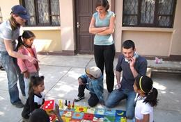 Professional Social Workers volunteering in Bolivia work through a therapeutic activity with local children.