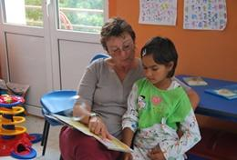 A professional Social Worker reads a book with a young child as part of her volunteer work at a daycare centre in Romania.