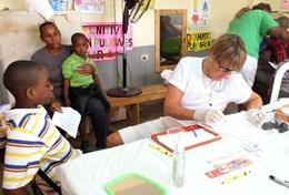 A qualified Dentist examines children's teeth during a dental outreach at her volunteer placement in Jamaica.