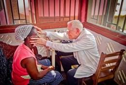 A professional medical Doctor performs health checks during a volunteer screening outreach at our placement in Ghana.