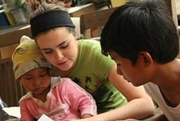 A professional Occupational Therapy volunteer works through a treatment regime with local children in Cambodia.