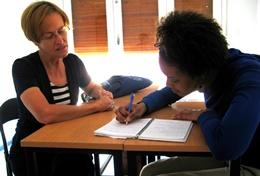 A professional Teacher works closely with a school student as part of her volunteer project abroad.