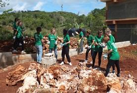 A group of Building volunteers works together to clear rocks from a building site in Jamaica over their Easter holiday.