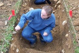 An Archaeology volunteer inspects the ground at a placement in Romania