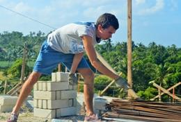A High School Special volunteer helps with building the framework for a house in the Philippines.