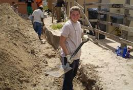 A High School Special Building volunteer assists with laying the foundation for a new house in South Africa.