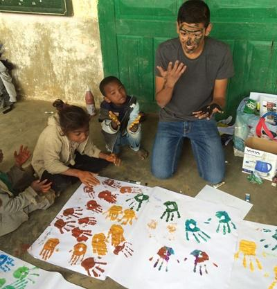 Care volunteer painting with the local children