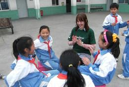 A high school volunteer sits in a playground in China with local children, playing an educational game with them.