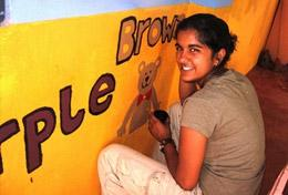 A High School Special volunteer paints an educational mural at a school as part of her Care & Community work in Sri Lanka.